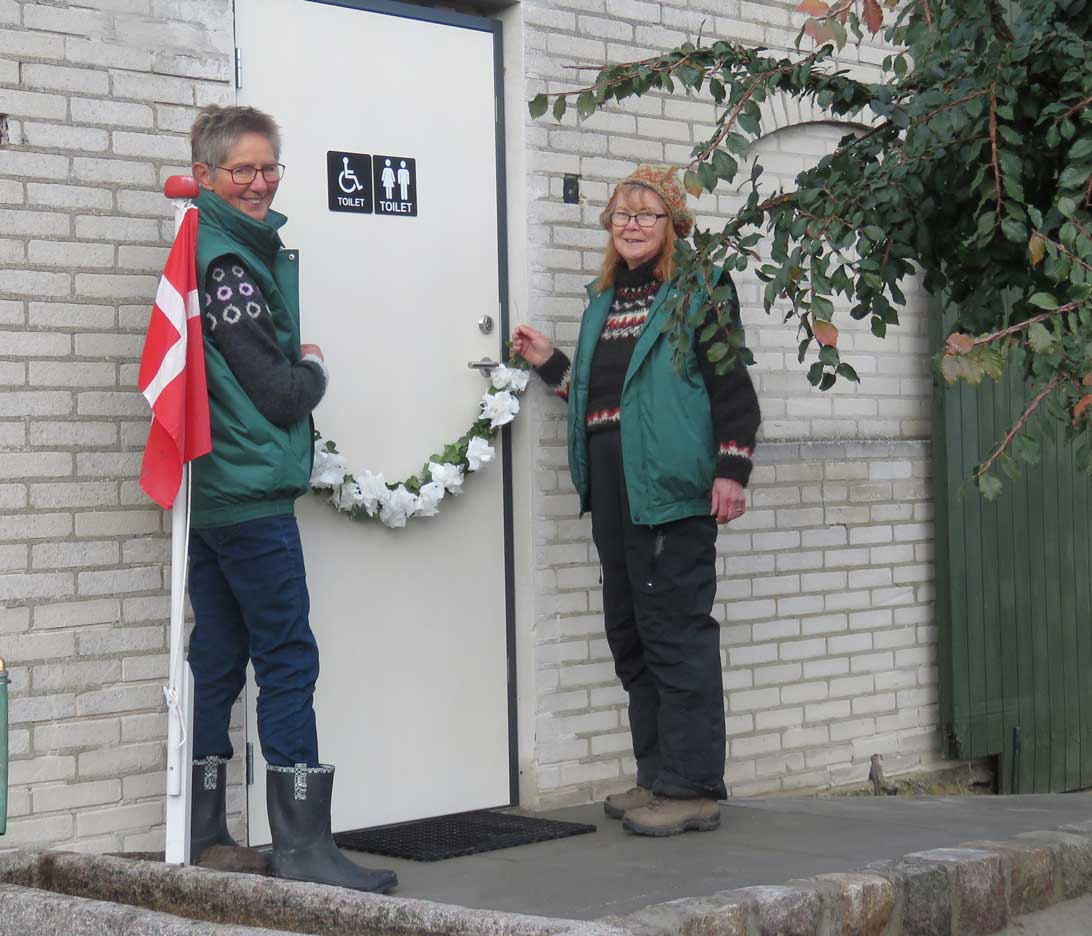 Bente Wulff og Gunvor Rosell hænger efeuranken på plads foran indgangen til toilettet, så den er klar til at blive klippet af Bo Nissen, formand for Trafik- Teknik- og Miljøudvalget i Langeland Kommune,